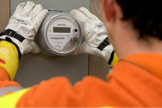 Utility worker installing a digital smart meter