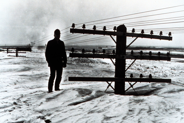Man on large snow bank next to power lines.