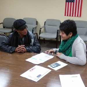 Ivonne, right, working with another consumer at a phone-bill clinic earlier this year.
